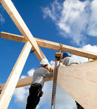 Authentic construction workers. Construction workers making a wooden  roof construction Royalty Free Stock Photo