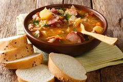 Authentic Czech cabbage soup with sausages and vegetables close-up in a bowl. horizontal. Authentic Czech cabbage soup with sausages and vegetables close-up in a stock photography