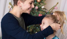 Authentic family christmas portrait in front of xmas tree. Smiling mother and daughter stock image