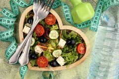 Free Authentic Fresh Salad In A Wooden Heart Shaped Cup With Dumbbells Excercise Equipment, Measuring Tape On Table. Healthy Lifestyles Stock Photos - 171490703