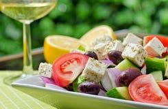 Authentic Greek Salad. An authentic greek salad with white wine stock photo