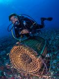 Traditional bamboo woven fish trap. Authentic image of a female diver hovering above an artisanal fish trap, or bubu, used by local subsistence fishermen to Royalty Free Stock Photo