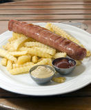 Authentic kielbasa Polish sausage with french fries Stock Image