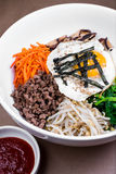 Authentic Korean Bibimbap. Rice bowl served with carrots, shitake mushrooms, sprouts, spinach, radish and beef. Topped with pan fried egg, seaweed, sesami oil Stock Photography