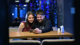 Authentic laughing casual teens in cafe using new application on smart phone. 4K stock footage