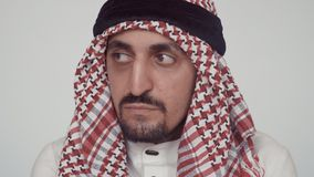Authentic modern Arab on white background. A man in national dress looks around and sighs sadly. The man has pronounced stock video footage