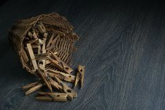 Authentic old wooden clothespins in a straw basket, on a dark wooden table. royalty free stock photo