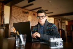Authentic portrait of young confident businessman looking at camera with laptop in office. Hipster man in glasses and Royalty Free Stock Image