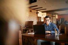 Authentic portrait of young smiling businessman looking at camera with laptop in cafe. Hipster like man in stylish. Glasses and smart casual shirt doing his Royalty Free Stock Photo