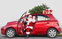 Authentic Santa Claus in car with gift boxes. And Christmas tree, view from outside stock images