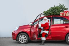 Authentic Santa Claus in car with gift boxes and Christmas tree. View from outside stock photography
