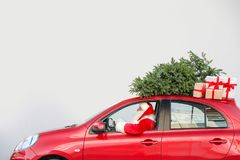 Authentic Santa Claus driving red car with gift boxes. And Christmas tree, view from outside stock images