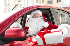 Authentic Santa Claus with gift box driving car,. View from outside royalty free stock image