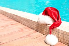 Authentic Santa Claus hat near pool. At resort royalty free stock images