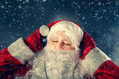 Authentic Santa Claus is listening to music. Authentic Santa Claus is listening to music on headphones. Christmas tale Stock Photos