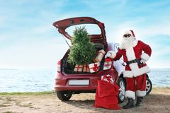 Authentic Santa Claus near red car with gift boxes. And Christmas tree on beach royalty free stock photos