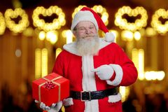 Authentic Santa Claus with present box. Male old Santa Claus pointing on red gift box holding in hand, festive lights background. New Year and Christmas time Royalty Free Stock Images