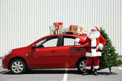 Authentic Santa near red car with gift boxes on it`s top. And Christmas tree Royalty Free Stock Images