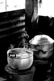 Authentic Thai Kitchen. Small pots rest on cook top of an authentic Thai kitchen.  Pot is steaming with hot liquid.  Photo is in black and white Stock Photography