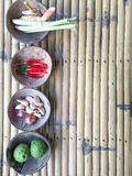 Authentic Thai red curry ingredients in coconut shells on bamboo table royalty free stock images