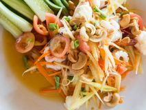 Authentic traditional salad with green papaya, fresh vegetables and herbs, seafood on plate in Thai restaurant. Authentic traditional salad with green papaya royalty free stock photos
