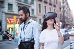 Couple or friends experience VR in the city. Authentic and trendy couple of millenials use augmented reality technology and VR headset in the busy city street Stock Photo