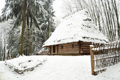 Authentic ukrainian village with wooden huts and fences in winter. Stock Image