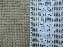 Authentic vintage rose pattern lace on burlap background. Royalty Free Stock Images