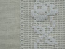 Authentic vintage rose pattern white lace on linen fabric background. Royalty Free Stock Photo