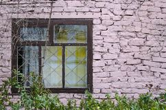 Authentic window frame of a rural cottage with pink brick wall and flowerpots mounted the grungy wall royalty free stock photos