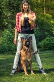 Authentic woman play with german shepherd dog in garden Stock Photography