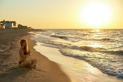 Authentic woman in swimsuit doing yoga padmasana on the beach in the morning. Real unretouched shape girl silhouette in stock image