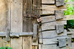 Authentic wooden door and a vintage lock on a rusty loop, concept of old objects royalty free stock photos