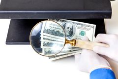 Authentication of banknotes using a magnifying glass Royalty Free Stock Photos