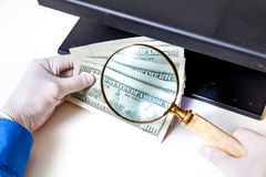Authentication of banknotes using a magnifying glass Royalty Free Stock Images
