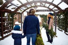 Authentieke familie dragende Kerstbomen en takken aan huis De de vadermoeder en dochter treffen voor Nieuwjaar voorbereidingen en stock foto