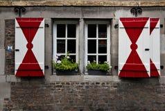 Authentieke houten rode & witte blinden op een middeleeuws huis stock foto