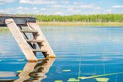 Authentieke houten trap en pijler dichtbij een schilderachtige vijverclos stock foto's