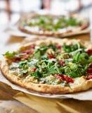 Authentieke oven in brand gestoken pizza met pestosaus en arugula stock foto