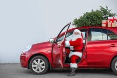 Authentieke Santa Claus in auto met giftdozen en Kerstboom stock fotografie