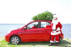 Authentieke Santa Claus die zich dichtbij zijn auto bevinden Stock Foto