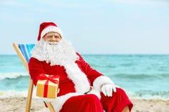Authentieke Santa Claus met giftdoos in ligstoel Stock Afbeeldingen