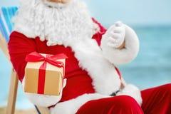 Authentieke Santa Claus met giftdoos in ligstoel Stock Afbeelding