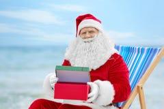Authentieke Santa Claus met giftdoos in ligstoel Stock Foto