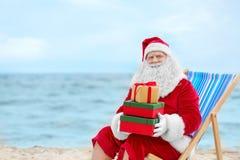 Authentieke Santa Claus met giftdozen in ligstoel Royalty-vrije Stock Afbeeldingen