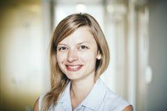 Authentische blonde Geschäftsfrau mit blauen Augen sicher lächelnd Stockfoto