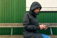 Authentische Frau in Winterjacke Schreibensms Mitteilung draußen Stockfotos