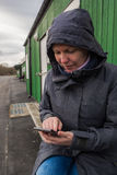 Authentische Frau in Winterjacke Schreibensms Mitteilung draußen Lizenzfreies Stockbild