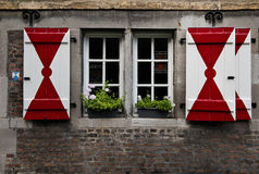 Authentische hölzerne rote u. weiße Fensterläden auf einem mittelalterlichen Haus Stockfoto