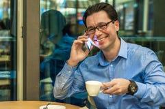 Authentisches Bild eines Geschäftsmannes, der in einem Kaffee arbeitet Bemannen Sie die Unterhaltung am Handy in einer Kaffeestub lizenzfreie stockfotografie